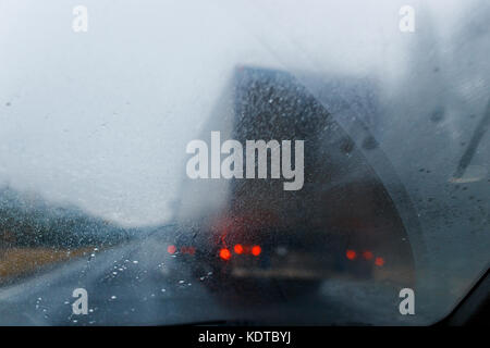 Rain drops on windscreen and blurred truck in forest road. Overtaking of the truck. Low visibility. - Stock Photo
