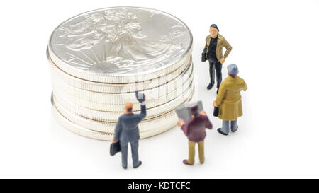 group of businessmen miniature figurines standing in front of silver american eagle coins on white background - Stock Photo