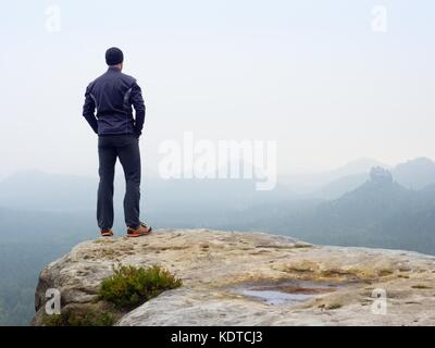 Nature hiker on sharp cliff roc watching over misty  valley to blurred horizon. Terrible rainy weather with thick - Stock Photo