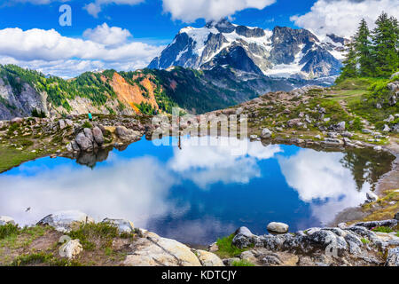 Hikers Mount Shuksan Pool Reflection Summer Artist Point Mount Baker Highway Pacific Northwest Washington State - Stock Photo
