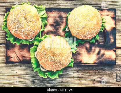 Hamburger on a wooden table. Rustic style, top view - Stock Photo