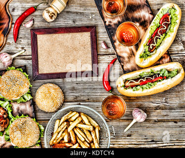Rustic style, top view homemade burgers with beef, hot dogs and beer on a wooden table. - Stock Photo