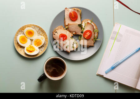 Healthy breakfast. Sandwiches with ham, arugula, butter, cherry tomatoes and hard-boiled eggs, black organic coffee - Stock Photo