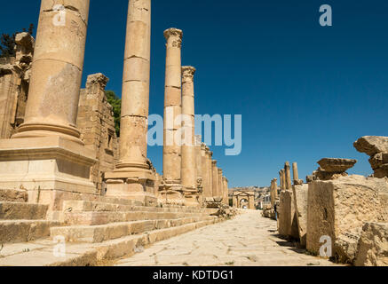 View of paved Cardo with Corinthian columns to North gate, Roman ruined city of Jerash, ancient Gerasa, archeological - Stock Photo
