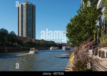 Private and commecial boats float on the north branch of Chicago river. - Stock Photo