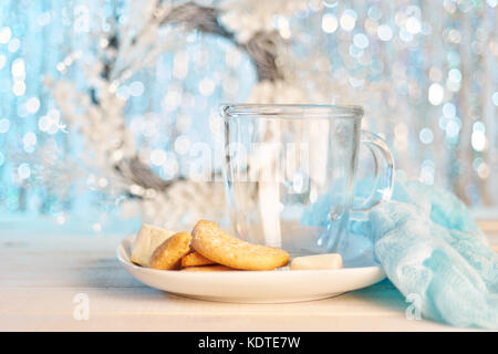Glass empty mug with cookies on light glitter background for Christmas. Copy space. - Stock Photo