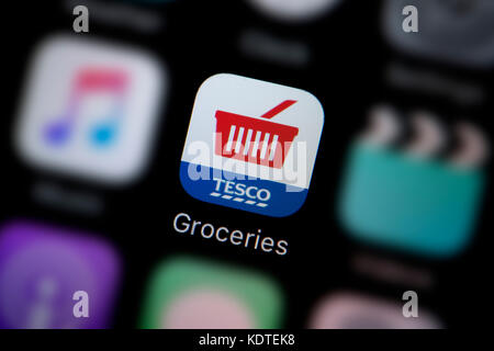 A close-up shot of the logo representing the Tesco Groceries delivery app icon, as seen on the screen of a smart - Stock Photo