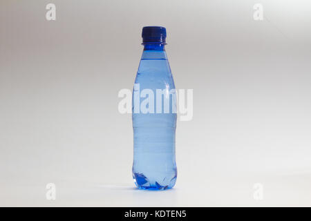 close-up of blue bottle of water against white background - Stock Photo