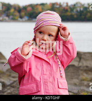 A little girl (3 yrs old) wearing a pink raincoat and hat - Stock Photo