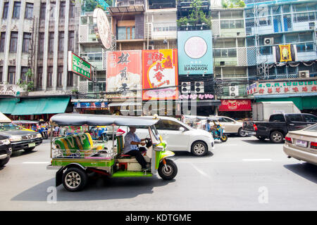 Tuk Tuk driving down Yaowarat Road, CHinatown, Bangkok Thailand - Stock Photo