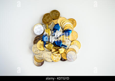 pile of colorful dreidels and Hanukkah coins isolated on white - Stock Photo