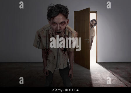 Scary two asian zombies come into dark room on abandoned house - Stock Photo