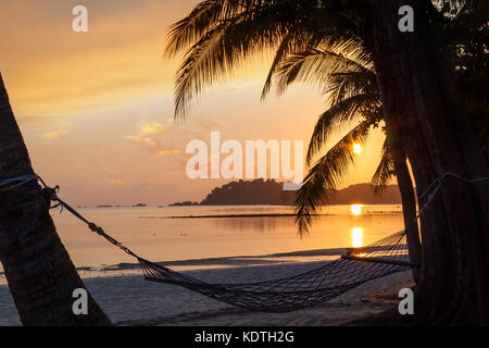Beautiful golden sunrise over sandy beach on Bintan Island in Indonesia with silhouette of hammock and coconut palm - Stock Photo