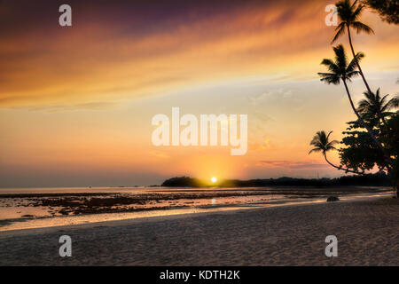 Beautiful golden sunrise over sandy beach on Bintan Island in Indonesia with silhouette of coconut palm trees with - Stock Photo