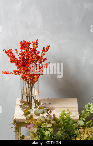 Ilex red. Dried branch in glass jug on wooden table and gray background. copy space - Stock Photo