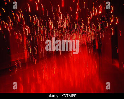 Red shining background lights with motion blur on black backdrop; template/texture with copy space; landscape format - Stock Photo