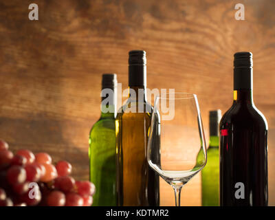 Romantic wine tasting atmosphere in a winery cellar with an empty wine glass in front of red grapes and wine bottles - Stock Photo