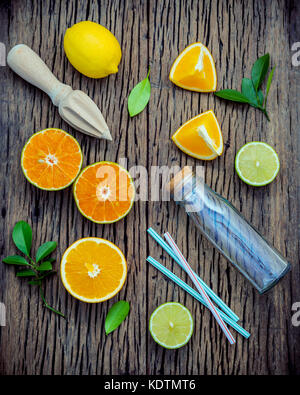 Mixed fresh citrus fruits and orange leaves background. Ingredients for summer citrus juice with juicer and glass - Stock Photo