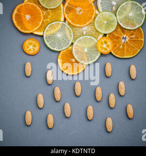 Healthy foods and medicine concept. Pills of vitamin C and citrus fruits in the shape of cloud and raining. Citrus - Stock Photo