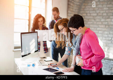 Group of young architects using digital tablet - Stock Photo