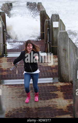 Aberystwyth, Ceredigion, Wales, UK  - Young woman runs from incoming waves on a jetty as high tide approaches at - Stock Photo