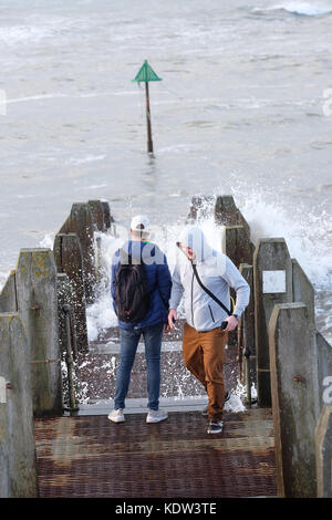 Aberystwyth, Ceredigion, Wales, UK  - Young friends run from incoming waves on a jetty as high tide approaches at - Stock Photo