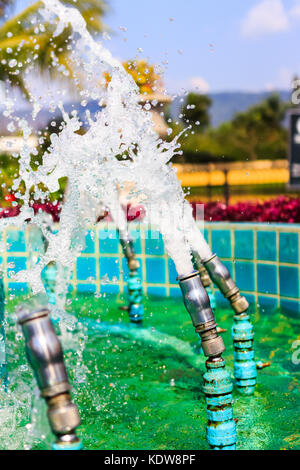 Closeup of fountain nozzles spraying water in a public park. - Stock Photo