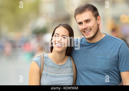 Front view of a happy couple walking on the street and looking away - Stock Photo