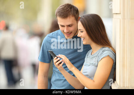 Happy casual couple checking content in a smart phone standing on the street - Stock Photo
