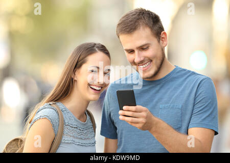 Happy couple enjoying using a smart phone standing on the street - Stock Photo
