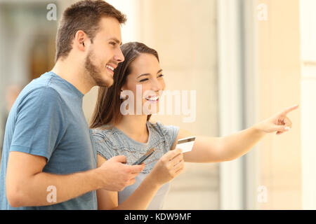On line buyers watching a storefront holding a smart phone and a credit card on the street - Stock Photo