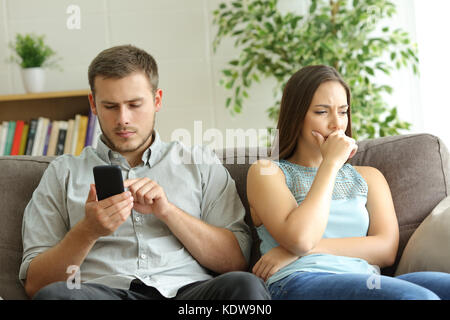 Husband addicted to smart phone watching content beside his worried wife looking down sitting on a sofa at home - Stock Photo