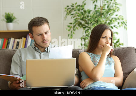 Husband addicted to work and unsatisfied wife beside him looking away sitting on a couch at home - Stock Photo