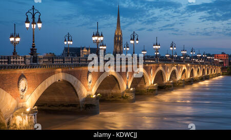 Pont de Pierre spanning the River Garonne at dusk with Basilique Saint-Michel beyond, Bordeaux, Aquitaine, France - Stock Photo