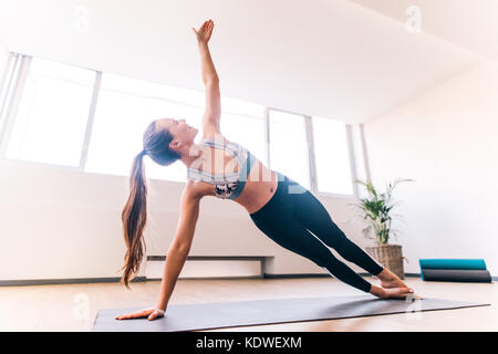 Slim woman in side plank pose at yoga class, Vasisthasana exercise. Female balancing on mat indoors at fitness gym - Stock Photo
