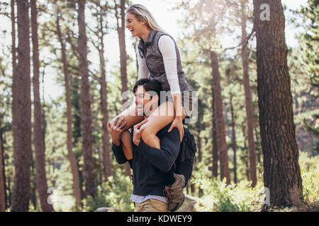 Hiking couple having fun while trekking in forest. Woman riding piggyback on man during hiking in forest. - Stock Photo