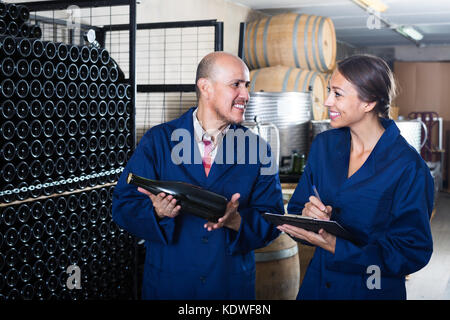 ... two friendly smiling winemakers in uniform examining bottle of wine winemaking cellar - Stock Photo  sc 1 st  Alamy & two smiling winemakers in uniform examining bottle of wine ...