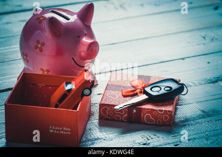 key of car and pink piggy bank in gift box on wood table - Stock Photo