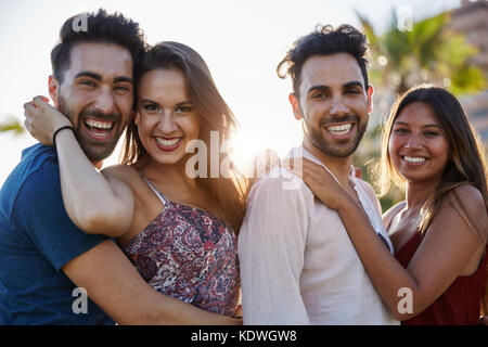 Portrait of two happy couples embracing together outside smiling - Stock Photo
