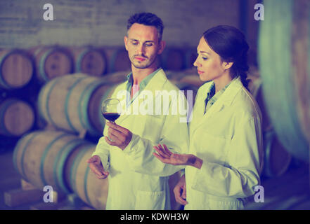 Portrait of young  positive  man and woman wearing coats holding glass of wine in winery cellar - Stock Photo