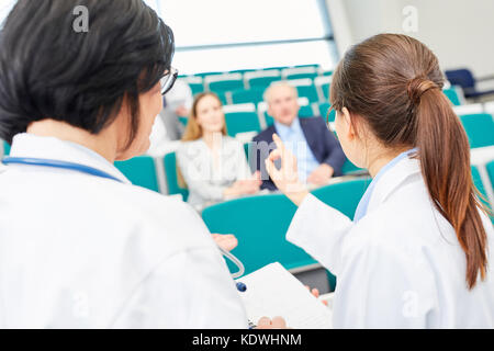 Young woman as student taking test in medical school - Stock Photo