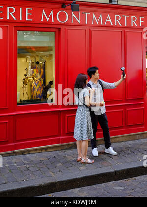 A young tourist couple take a selfie or shoot video using their gopro camera in Montmartre, Paris - Stock Photo