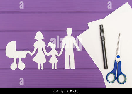 The silhouettes cut out of paper of man and woman with child and pram, scissors and marker near on a white sheet - Stock Photo