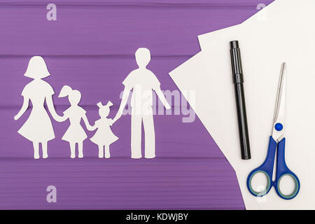 The silhouettes cut out of paper of man and woman with two girls, scissors and marker near on a white sheet of paper - Stock Photo