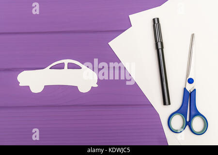 The silhouettes cut out of paper of car, scissors and marker near on a white sheet of paper on purple wooden background, - Stock Photo