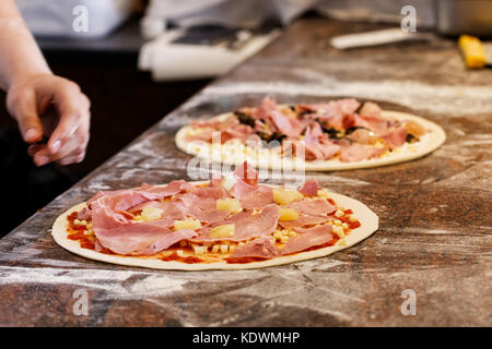 Cook putting toppings on two pizzas. - Stock Photo
