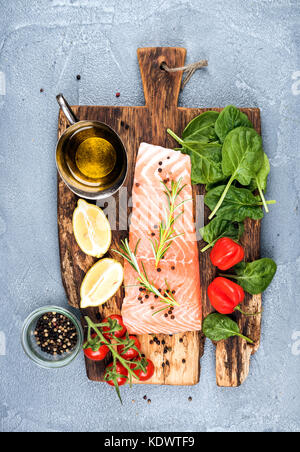 Ingredients for cooking healthy dinner. Raw salmon fillet, spinach, tomatoes, olive oil, lemon, peppers, rosemary - Stock Photo