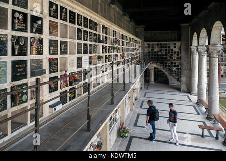 Tourists visit the Columbarium in Pere Lachaise cemetery in Paris, France. - Stock Photo