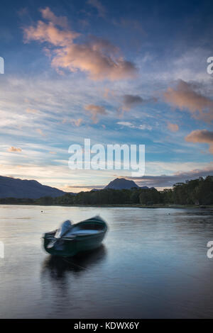 Dawn breaking over a boat moored on Loch Maree, with Slioch beyond, Wester Ross, Scotland - Stock Photo