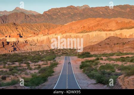A solitary car on the road down the Quebrada de la Conches, Valles Calchaquies, Salta Province, Argentina - Stock Photo